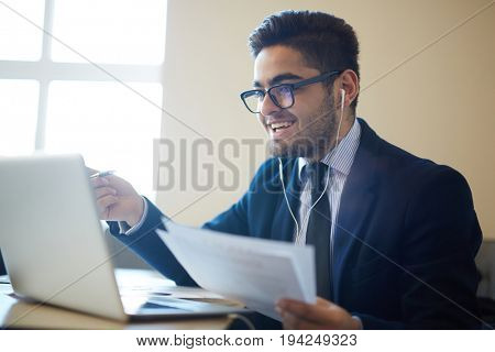 Happy trader with papers reading online information