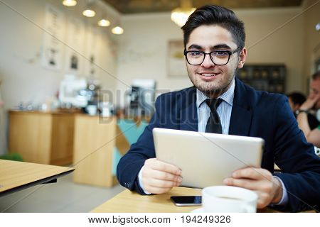 Young manager with touchpad spending time in cafe