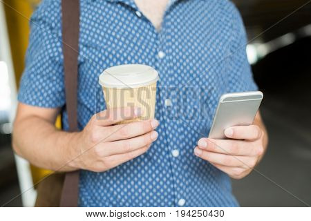 Close Up Of Man With Takeaway Coffee Texting On Mobile Phone