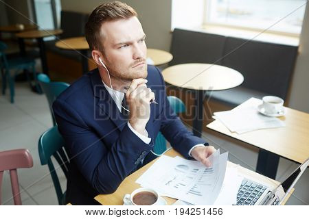 Pensive economist analyzing financial papers