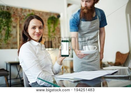 Young businesswoman sharing data in smartphone with waiter near by