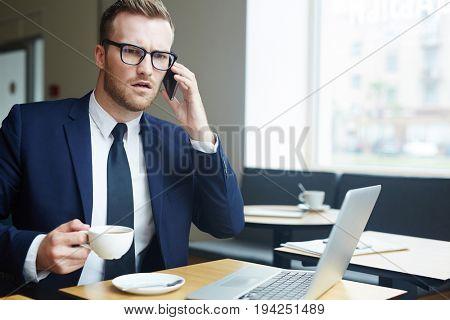 Modern broker talking by smartphone in cafe