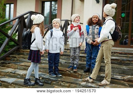 Group of children chatting standing on schools doorstep, all wearing backpacks and similar knit clothes