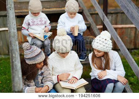 Group of children playing outdoors in countryside: sitting on wooden steps of village house and reading books all dressed in similar knit clothes