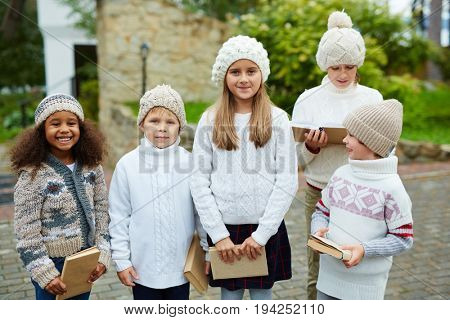 Children of various ages posing outdoors smiling to camera and holding books, all dressed in similar knit clothes