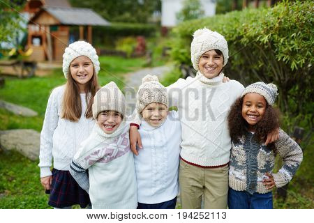 Happy children of various ages standing close together and looking at camera smiling, dressed in matching white knit clothes posing as siblings or family