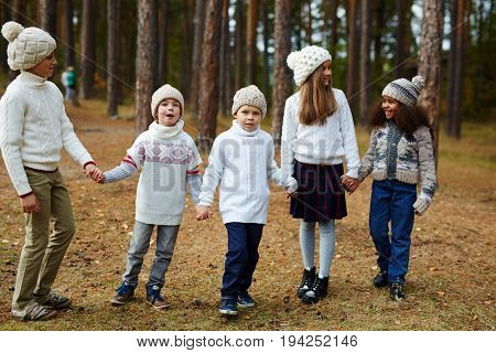 Group of children walking in pine forest holding hands on warm autumn day, posing as siblings all wearing similar knit clothes