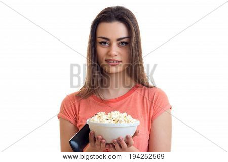 beautiful woman with a plate of pop corn and remote control looks into the camera and smiling isolated on white background