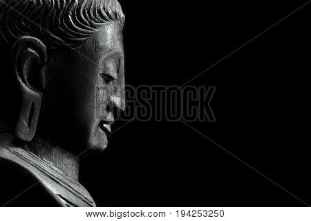 Wooden buddha profile isolated on a black background.