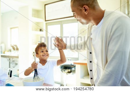 Father And Son High Fiving While Baking In The Kitchen