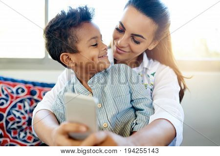 Smiling Mother And Son Taking A Selfie Together At Home