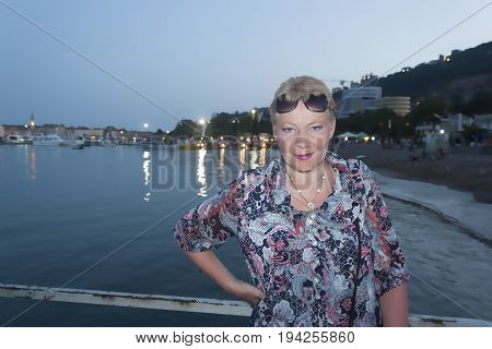 A Mature Woman On The Background Of Evening Lights