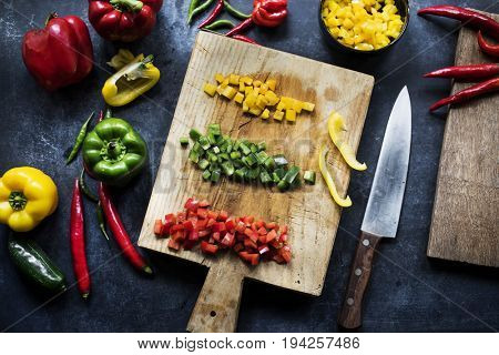 Chopped variation bell pepper on a wooden cutting board