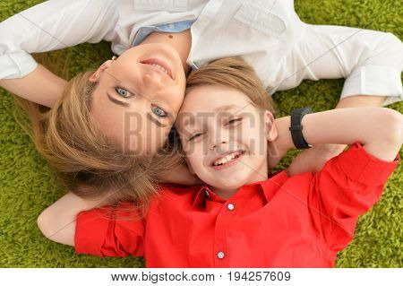Smiling mother and son lying on floor with green carpet