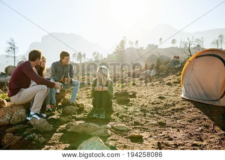 Group of young friends sitting on rocks and talking together while enjoying coffee at their campsite in the early morning