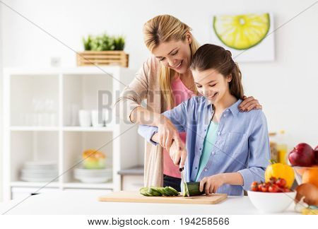 cooking food, healthy eating, family and people concept - happy mother and daughter chopping vegetables for dinner at home kitchen
