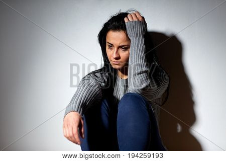 people, grief and domestic violence concept - unhappy woman sitting on floor and crying
