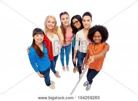 diversity, race, ethnicity and people concept - international group of happy smiling different women over white taking picture with selfie stick