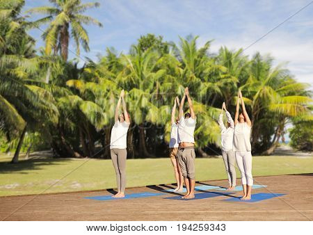 fitness, sport, yoga and healthy lifestyle concept - group of people making upward salute pose over natural exotic background with palm trees