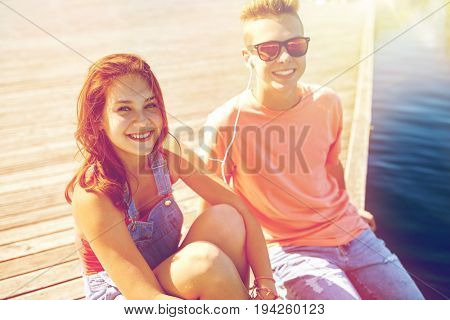 holidays, vacation, love and people concept - happy teenage couple with earphones sitting on river berth and listening to music at summer