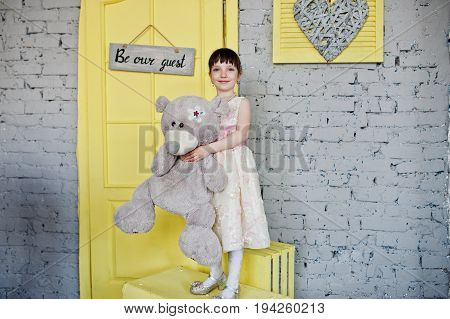 Little Cute Girl In A Beautiful Dress With A Toy In Her Hands Posing On The Yellow Wooden Boxes Next