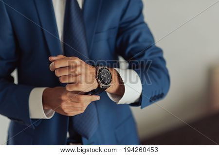 Closeup of a hand groom buttoning cuffs his hands and cufflink on his suit. Instagram colors toning