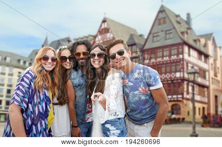 travel, tourism and people concept - smiling young hippie friends taking selfie by monopod over frankfurt am main city street background