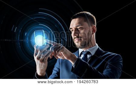 business, augmented reality and future technology concept - businessman in suit working with transparent smartphone and hologram over black background