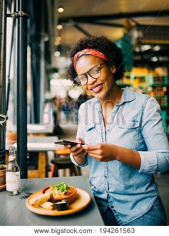 Smiling Woman Taking Photos Of Her Meal In A Cafe