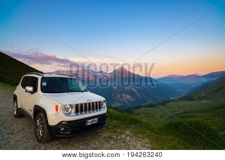 Colle delle Finestre, Italy - June 22, 2017: White Jeep Renegade parked on dirt road at panoramic view point on the Italian Alps from above. Colorful sky at sunset mist on the valley below.