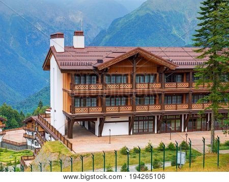View on Swiss cottage chalet style wooden architecture hotels among green mountains hills in Krasnaya Polyana near to Adler and Sochi. Russian holidays vacation tours ski and snow board sports