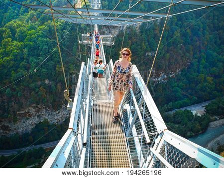 SOCHI, RUSSIA, SEP, 05, 2015: Pretty young girl on SKYPARK metal bridge stair staircase above river. SKYPARK MegaTroll and bangee jumping Sochi adrenaline for tourists. Best holiday vacation tours
