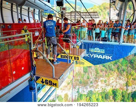 SOCHI, RUSSIA, SEP, 05, 2015: SKYPARK staff  prepares young girl for bungee jumping - jump from the bridge and people tourists. Sochi sightseeing holiday vacation best tours travel. Krasnaya Polyana