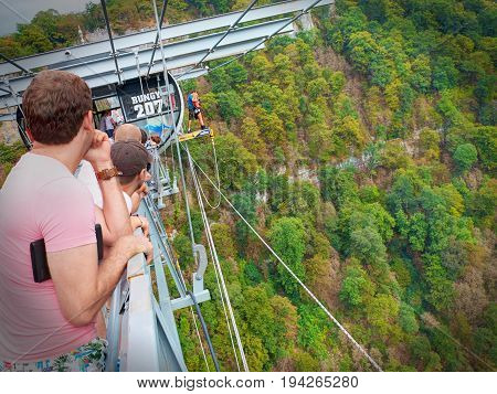 SOCHI, RUSSIA, SEP, 05, 2015: SKYPARK staff  prepares young girl for long bungee jumping - jump from the bridge and people tourists. Sochi holiday vacation best tours travel. Adrenaline entertainment