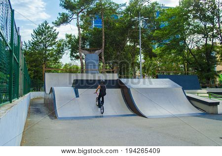 Extreme BMX rider in helmet jump in skatepark on competition. Sport bicycle concept for billboard. Brave and strong man making tricks.