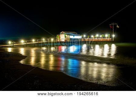 Summer night evening view on highlighted pier with open sea restaurant for romantic diners. Lights water reflection. Greece Islands romantic holidays vacations famous tours. Bali, Bahamas, Maldives