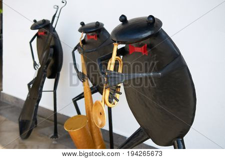 BELEK, TURKEY, SEP. 10, 2010: Three black metal frog sculptures music orchestra Jazz band at white wall. Funny metal frogs with red bow tie with saxophone, grunt-horn, bass viol