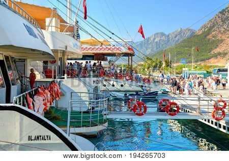 TURKEY, ANTALIA, SEP.10, 2010: View on people tourists boarding on touristic sightseeing white yachts boats to famous waterfall. White boats ships at pier Turkey holidays vacations tours criuise