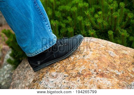 close up of feet walking step by step overcoming obstacles moving into bright future success. one person climbing over rock stones .