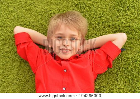 Portrat of blonde little boy lying on green carpet in room