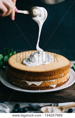 Making of Sponge Cake with Strawberry. Hand putting icing on freshly baked cake