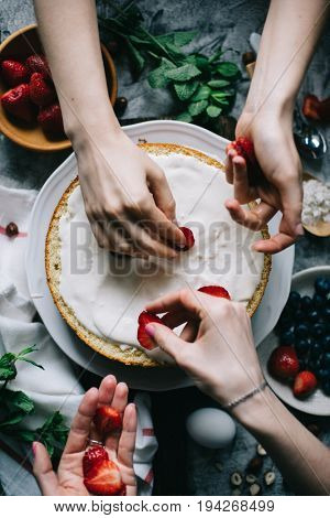 Two young women making strawberry sponge cake, closeup view of hands decorating cake