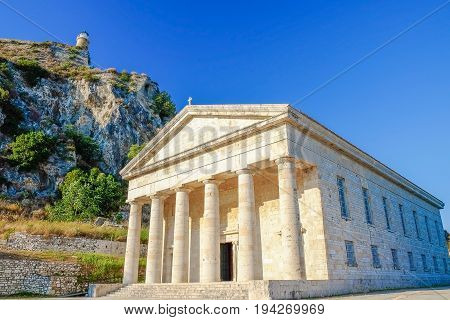 KERKYRA CORFU GRECE - JULY 5 2017: St. George's Church in the Old Fortress with an old lighthouse and blue sky on the background.