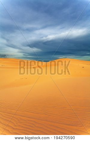 Sand dunes and mountains of the desert. evening at sunset. The dramatic clouds.