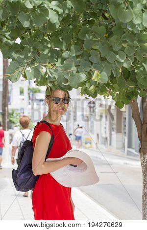 Woman in red dress, sunglasses, backpack, holding white hat in hand, standing under the tree, looking to camera