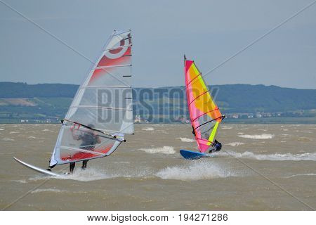 Two windsurfers on Lake Neusiedl fully in motion - Austria