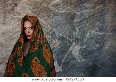 Beautiful Muslim Woman portrait in Hijab. Close up of beauty arabian woman with perfect makeup and manicure isolated on abstract mountain background. Traditional muslim dress hijab burka niqab