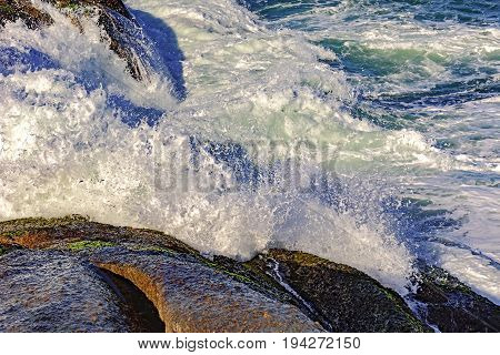 Sea water drops and spray over the stones of the Arpoador beach