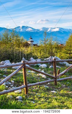 Landscape with the wooden fence, spring trees, wooden tower of chalet and snowy peaks of mountains in Bansko, Bulgaria
