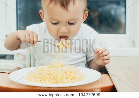 The Child Greedily Eating Pasta